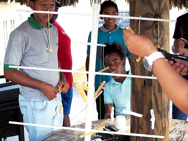 Jong Bonaire students learning how to hang and tie corals on nursery trees.